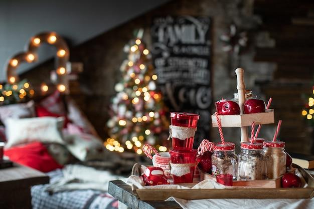 Czerwone świąteczne kubki ze słodyczami są na stole na tle choinki