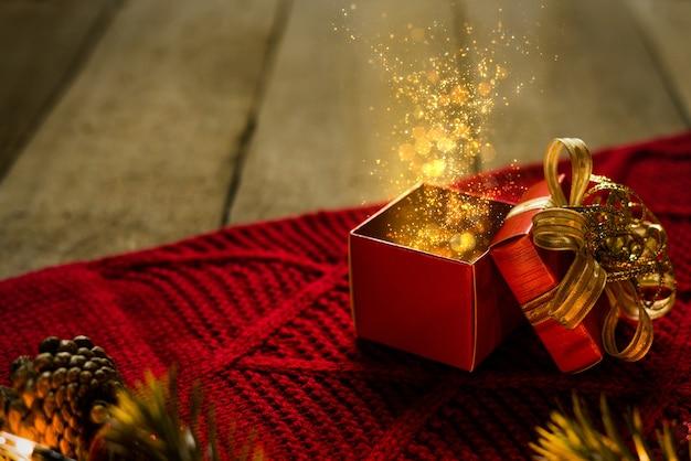 Czerwone świąteczne pudełko na czerwonym scrafie ze złotymi drobinkami świeci magicznie na drewnianym biurku.