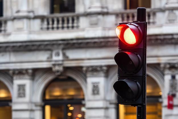 Czerwone światła dla samochodów na niewyraźnych budynkach