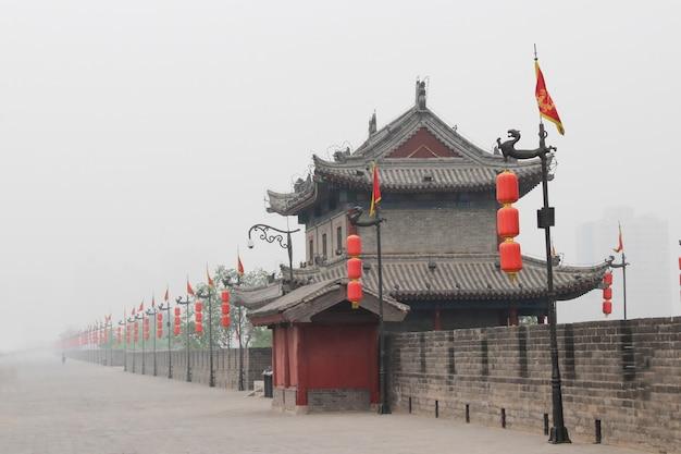 Czerwone światła wzdłuż ściany z cegły. mgła. starożytny budynek. chiny