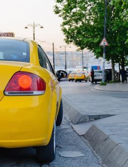 Czerwone światło hamowania żółte taksówki na tle wieczoru w stambule