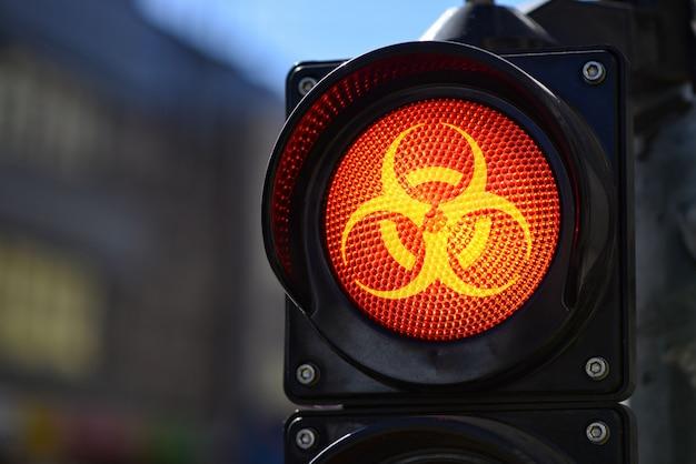Czerwone światło semaforowe z symbolem ostrzegającym o zagrożeniu biologicznym, koncepcja ochrony covid-19
