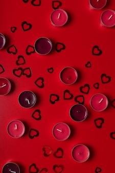 Czerwone świece i serca na czerwonym tle