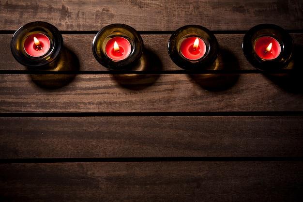 Czerwone świece na drewnianym stole.