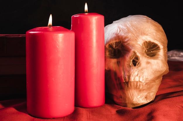 Czerwone świeczki i czaszka w plastikowym worku