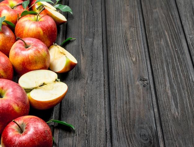 Czerwone świeże jabłka i plasterki jabłka. na drewnianym tle.