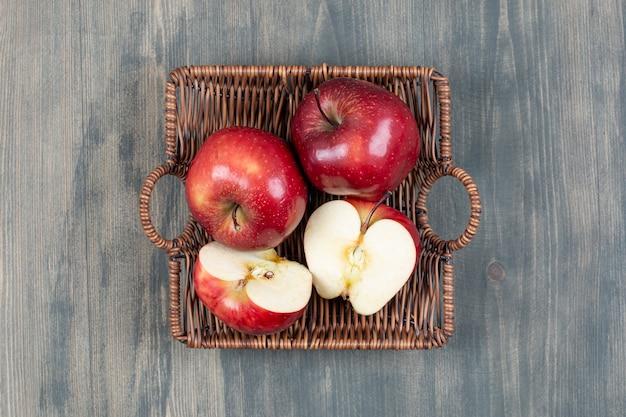 Czerwone świeże jabłka w drewnianym koszu