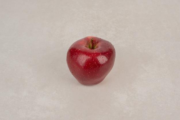 Czerwone, świeże jabłko na białym stole.