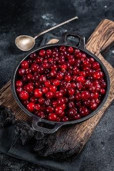Czerwone świeże jagody żurawinowe na patelni. czarne tło. widok z góry.