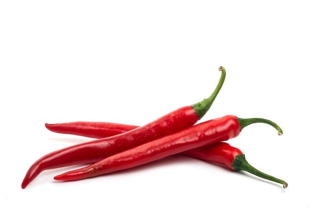 Czerwone świeże papryki chili na białym tle.