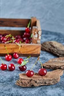 Czerwone świeże soczyste wiśnie w drewnianym pudełku z liśćmi
