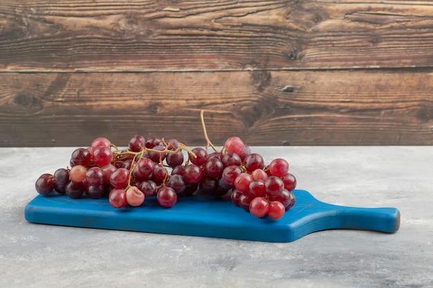 Czerwone, świeże winogrona umieszczone na niebieskiej desce do krojenia.