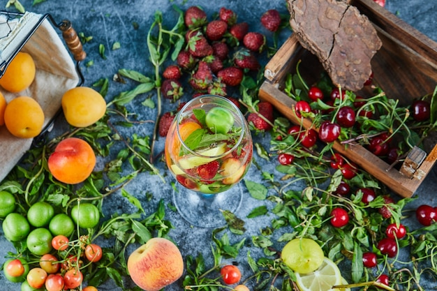 Czerwone świeże wiśnie na drewnianym pudełku ze szklanką soku owocowego i świeżych owoców