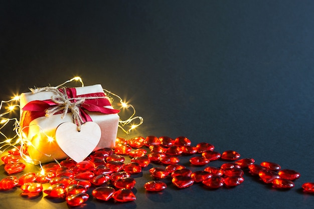 Czerwone szklane serduszka i miękkie pluszowe serce z napisem love na czarnym stole