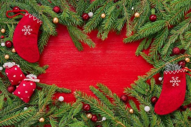 Czerwone tło boże narodzenie. gałęzie choinkowe i czerwone skarpetki świąteczne na czerwonym tle drewnianych. kopiowanie miejsca, widok z góry