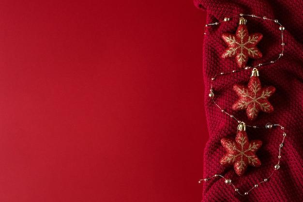 Czerwone tło boże narodzenie z czerwonymi zabawkami świątecznymi i koralikami na czerwonej dzianinie.