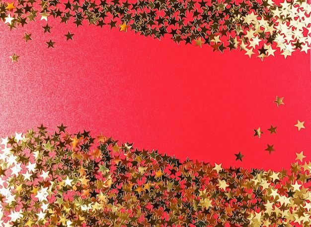 Czerwone tło boże narodzenie ze złotymi gwiazdami. widok z góry, układ płaski