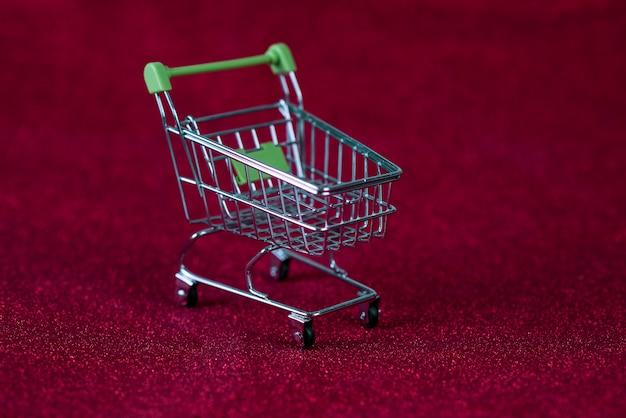 Czerwone tło i wózek na zakupy koncepcja zakupów i handlu