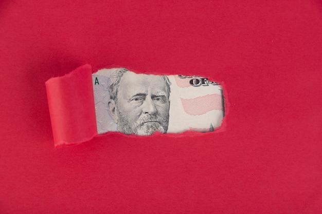 Czerwone tło, spod którego zagląda portret pięćdziesięciu dolarów. koncepcja pieniędzy pożyczonych