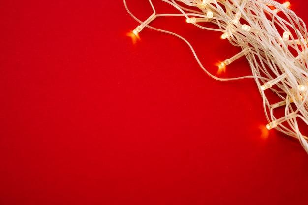 Czerwone tło z oświetlonymi światłami girlandy