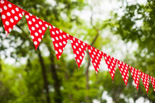 Czerwone trójkątne flagi z białymi kropkami na tle przyrody
