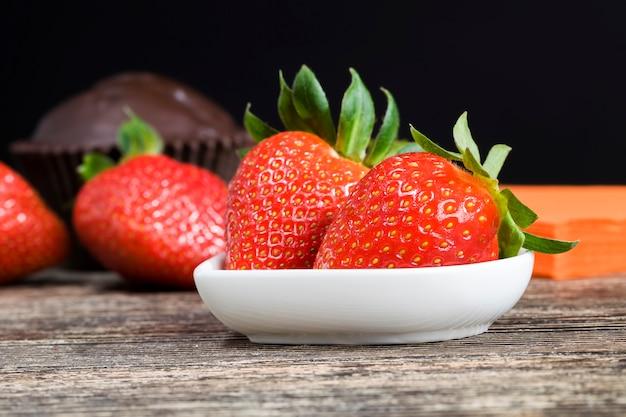 Czerwone truskawki i czekoladowa babeczka