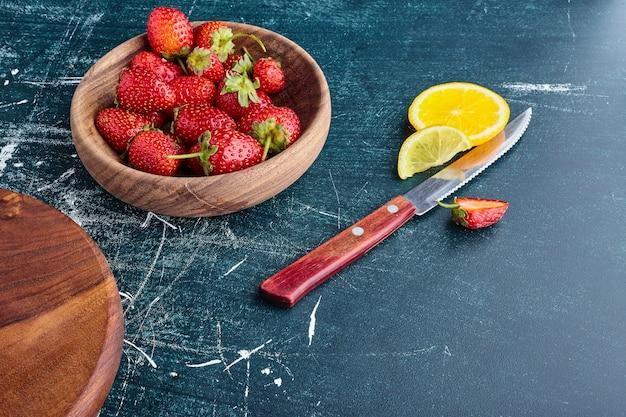 Czerwone truskawki w drewnianej filiżance z plasterkami cytryny na bok.