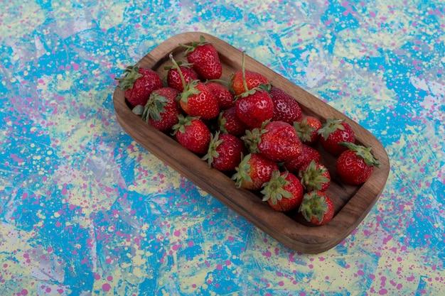 Czerwone truskawki w drewnianym talerzu na niebieskim tle