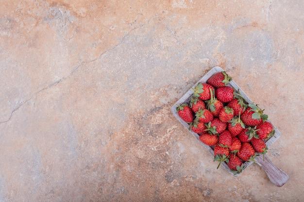 Czerwone truskawki w rustykalnym drewnianym talerzu na marmurze