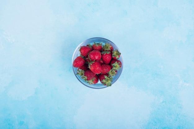 Czerwone truskawki w szklanej filiżance na niebiesko
