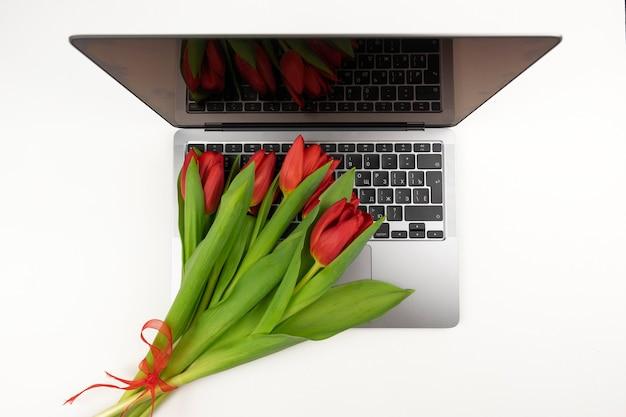 Czerwone tulipany leżą na laptopie z okazji międzynarodowego dnia kobiet