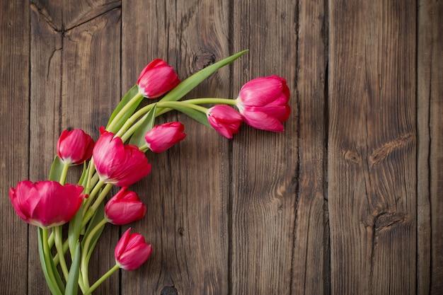 Czerwone tulipany na ciemnym tle drewnianych