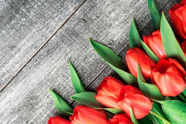 Czerwone tulipany na czarno-białym tle drewna, płaski widok z góry