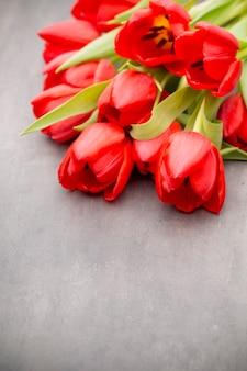 Czerwone tulipany na drewnianej powierzchni.