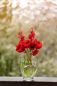 Czerwone tulipany na drewnianym parapecie