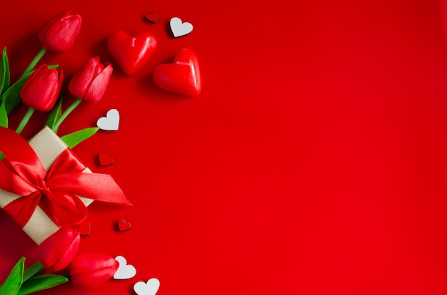 Czerwone tulipany, pudełka i drewniane serca na czerwonym tle. kartkę z życzeniami na walentynki.