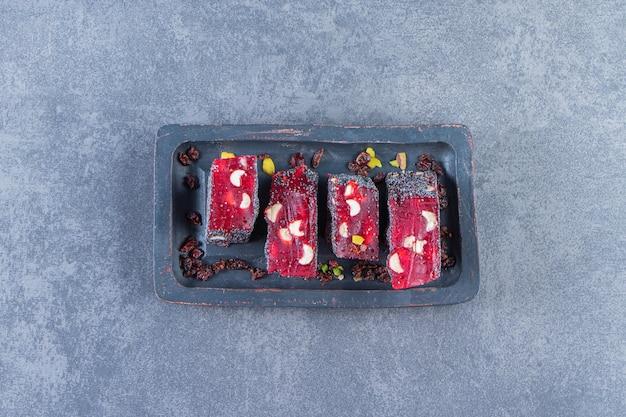 Czerwone tureckie rozkosze w drewnianym talerzu, na marmurowej powierzchni
