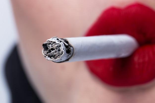 Czerwone usta palące papierosa z bliska
