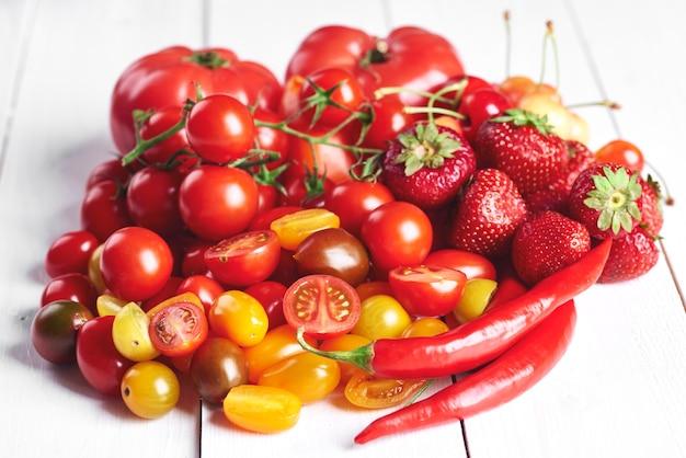 Czerwone warzywa i owoce na białym drewnie