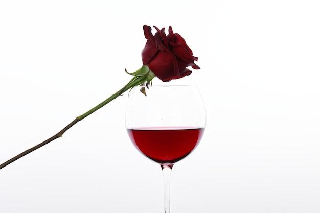 Czerwone wino i czerwona róża przed białą ścianą