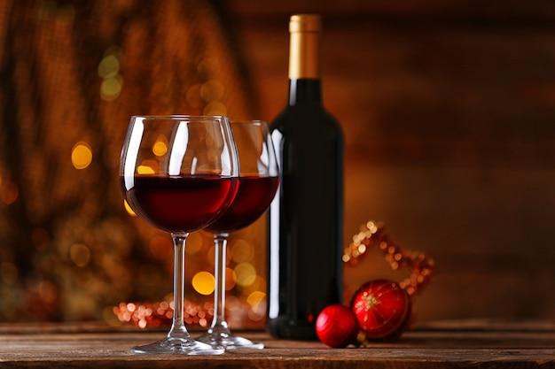 Czerwone wino i ozdoby świąteczne na drewnianym stole na drewnianym tle