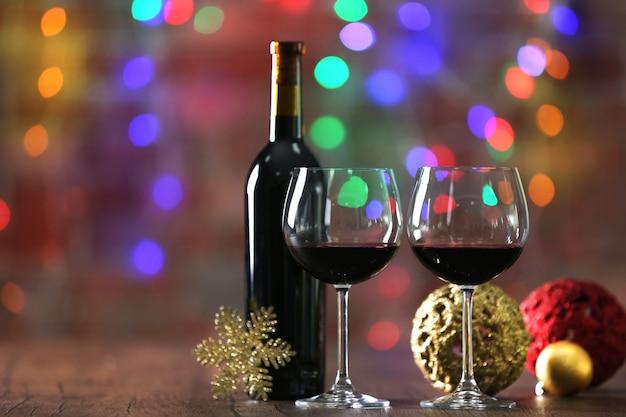Czerwone wino i ozdoby świąteczne na drewnianym stole na powierzchni lampek choinkowych