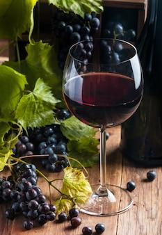 Czerwone wino i winogrona w stylu vintage na drewnianych