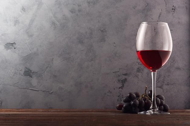 Czerwone wino i winogrona. wino i winogrona w rocznika położeniu z korkami na drewnianym stole