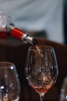 Czerwone wino leje do kieliszka wina, szczelnie-do góry