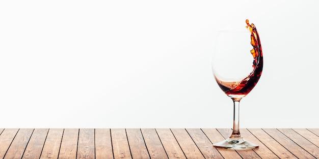 Czerwone wino nalewane do kieliszka na białym tle