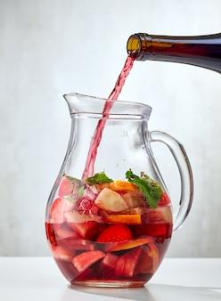 Czerwone wino nalewanie do dzbanka pokrojonych owoców. proces robienia czerwonej sangrii