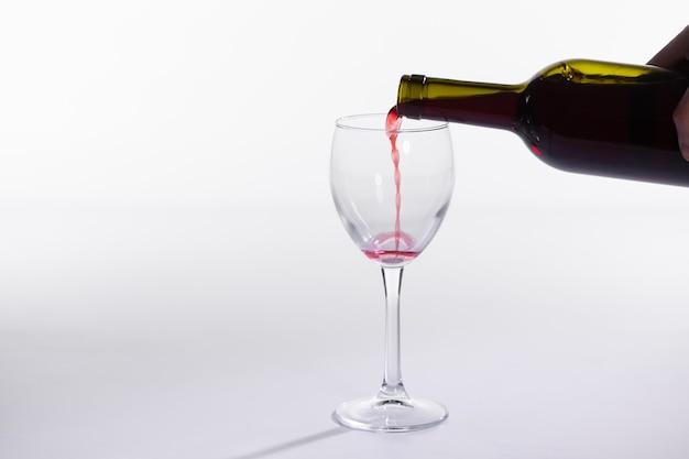 Czerwone wino nalewanie do szklanki z butelki na białym tle z miejscem na kopię