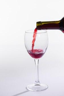Czerwone wino nalewanie do szklanki z butelki na białym tle