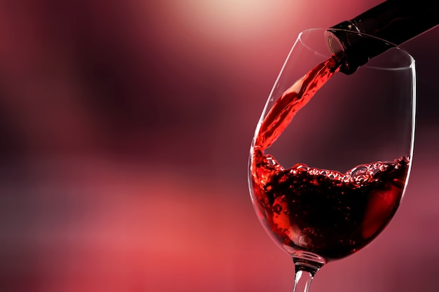 Czerwone wino nalewanie z butelki w kieliszku